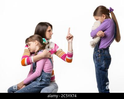 Mom talks hard with her daughter for offending her sister. - Stock Photo