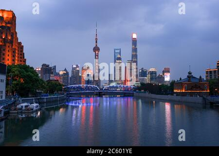 Night view of Waibaidu bridge and Lujiazui, the landmarks of Shanghai, China, with reflection in front. - Stock Photo