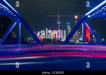 Night view of Waibaidu Bridge, a landmark steel bridge in Shanghai, with traffic and modern skyscrapers in the back.