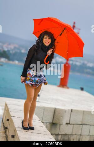 Teen girl with Red umbrella in hands - Stock Photo