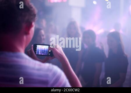 taking smartphone photo at party in night club