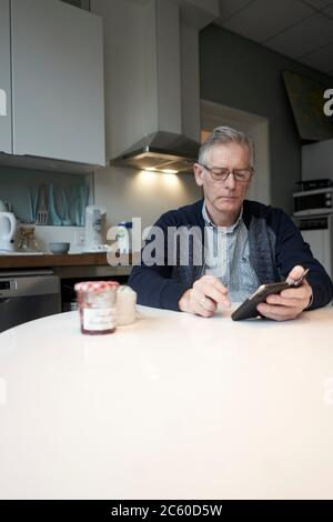 senior man using smartphone at breakfast table in kitchen. - Stock Photo