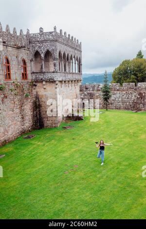 Young female tourist running on grass on the Soutomaior Castle in Galicia, Spain