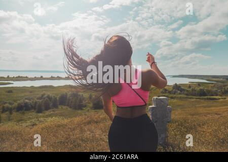 girl in sports let loose her hair after climbing a mountain Stock Photo