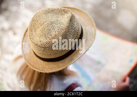 Woman traveler is looking at city map at town street in Europe. Girl tourist is searching destination