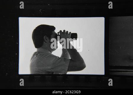 Fine 70s vintage contact print black and white photography of a man looking thru his binoculars while on the job.