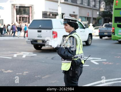 NYPD traffic control officer seen on the busy streets of New York in a typical busy time of day. - Stock Photo