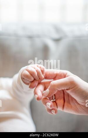 Baby holding mother's finger. Close up