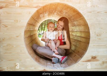 Mother and baby sitting in a wooden tunnel. Eco-friendly playground. Soft light - Stock Photo
