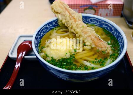 Tempura udon, with eggs and chikawa in a clear soup, topped with minced onion Placed in a black tray with a spoon placed beside the bowl.