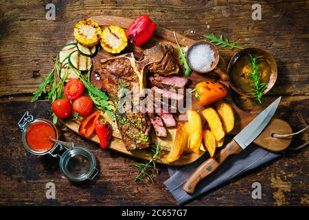 Beef steak with grilled vegetables and seasoning on serving board - Stock Photo