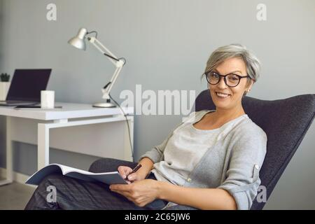 Happy senier woman in glasses writes a text in a textbook sitting in a chair at home. Work and education for people of age. - Stock Photo