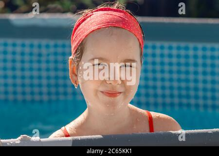 Beautiful little girl having fun outside in summer garden. Lovely smiling girl in kiddie pool at summer sunny day. Activities with children outdoors. - Stock Photo