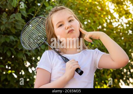 A little girl jokingly makes a glamorous face. Cute little girl playing badminton outdoors on warm and sunny summer day.