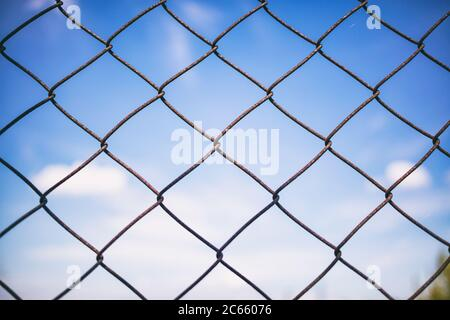 Blue sky with clouds through rusty wire mesh fence. Protection border and forbidden line. Blur background, texture. Close up view of link cage, wallpa