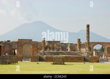 Temple of Jupiter. North End of the Forum,  Ancient Roman Pompeii . Ruins with Mount Vesuvius in the background. Pompeii, Italy. Europe. - Stock Photo