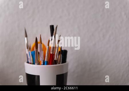 Art supplies containing bunch of paint brushes in a cup - Stock Photo