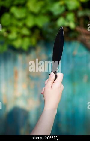Black knife for throwing in the hand of a woman, game for active recreation - Stock Photo