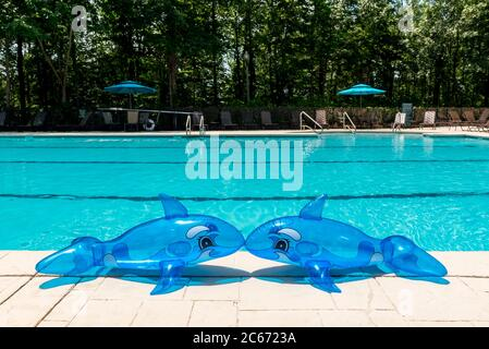 Inflatable pool toys on the deck of a poll with the water in the background. - Stock Photo
