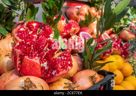 Ripe and juicy half peeled pomegranates ready to be squeezed for fresh juice Stock Photo