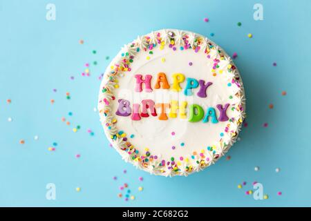 Happy birthday cake with rainbow lettering - Stock Photo