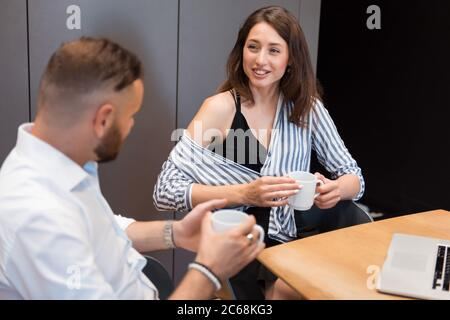 Two office workers having conversation while drinking coffee - Stock Photo