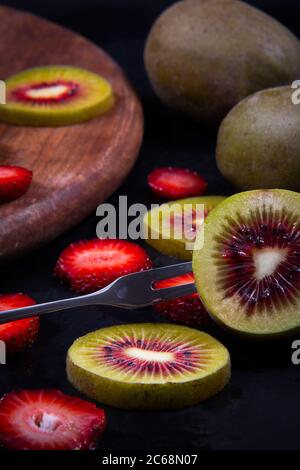 Close view of tiny fruits, green and red kiwis, and a red ripe strawberry.