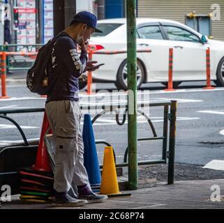 Man smoking in a designated smoking area, Nakameguro, Tokyo, Japan - Stock Photo