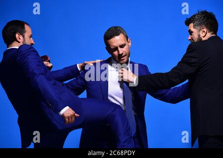 Business opposition and competition concept. Company leaders fight for business leadership. Businessmen with strict faces in formal wear on blue background. Coworkers decide upon best working position - Stock Photo