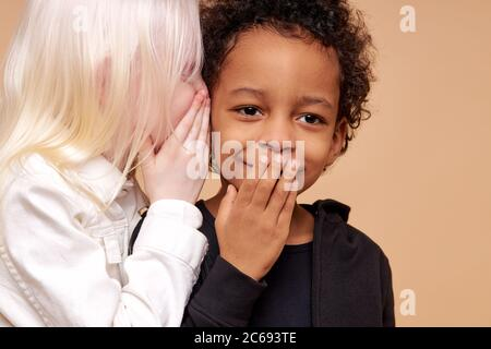 portrait of surprised afro boy and positive albino girl having secret. friendly girl tell story in boy's ears, boy stand in shock closing mouth - Stock Photo