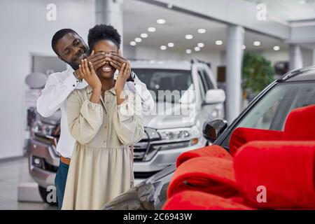 black man prepared gift to his wife, going to give new auto as a present, man closed woman's eyes during surprise. luxurious car is wrapped in red bow - Stock Photo