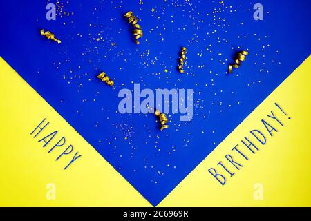 Golden decorations and sparkles on bright blue yellow background. As fireworks, happy birthday lettering. - Stock Photo