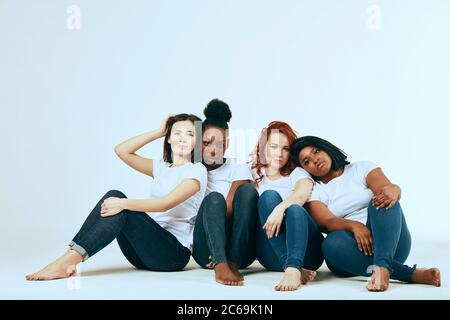 friendship, fashion, body positive, diverse female beauty concept - group of happy multicultural different size women in casual wear posing on white b - Stock Photo