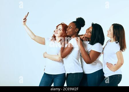 friendship, fashion, body positive, diverse female beauty concept - group of happy multicultural different size women in casual wear making selfie on