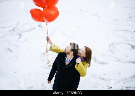 caucasian couple take a walk at winter street, celebrating saint valentines day outdoors. happy man and woman with red air balloons, on a romantic dat