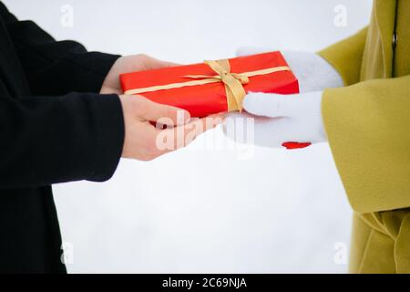 close-up hands of couple, caring man in love giving gift to his girlfriend. man give small red gift box to lady in white gloves. st valentines day, an - Stock Photo