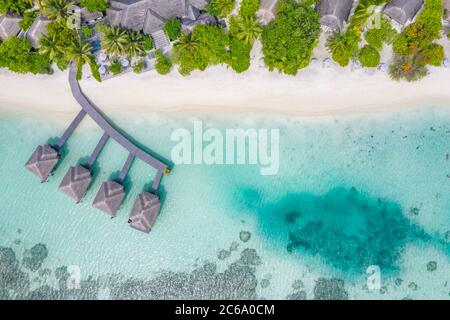 Perfect aerial landscape, luxury tropical resort or hotel with water villas and beautiful beach scenery. Amazing bird eyes view in Maldives, landscape - Stock Photo