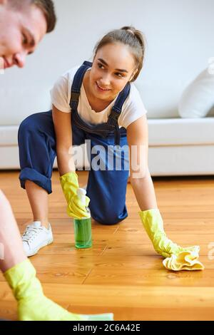 Young caucasian female wearing uniform, using rag and spray, polish wooden floor, white leather sofa background. Girl janitor look at colleague - Stock Photo