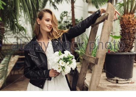 Young attractive smiling woman in black leather jacket and white dress with little bouquet of flowers in hand, near wood ladder happily looking aside - Stock Photo