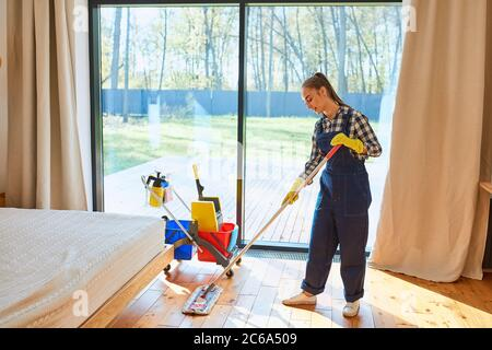 Enjoying cleaning service job. Young beautiful janitor cleaner in blue uniform with cleaning equipment stand mopping the floor in bedroom. Big panoram - Stock Photo