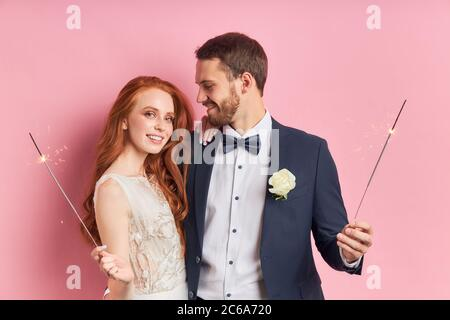 Caucasian couple wearing tuxedo, white wedding dress. Happy two people hold sparklers in hands. Love concept - Stock Photo