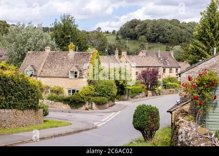 Old stone cottages in the Cotswold village of Naunton, Gloucestershire UK - Stock Photo