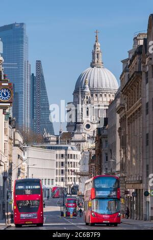 Red double-decker buses on Fleet Street with the dome of St. Paul's Cathedral and skyscrapers in the financial district of City of London, London, Eng