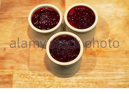 Homemade cheese cake with red fruit jam made in ceramic jars, selective focus - Stock Photo