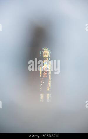 BRITANNY, FRANCE - AUGUST 4, 2018: Stained glass window depicting Saint Francis of Asisi seen through keyhole in closed church door. Mystic background - Stock Photo
