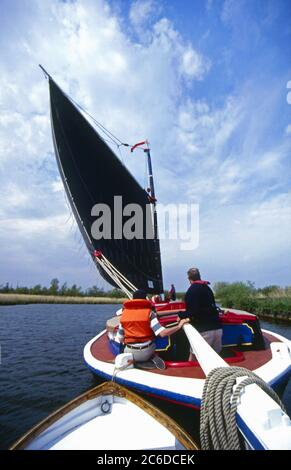 Wherry Albion sailing on river Bure, seen from towed dinghy, Norfolk Broads, England - Stock Photo