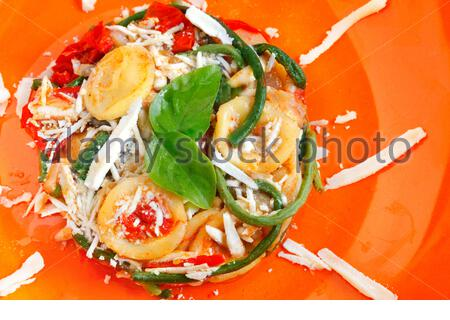 Traditional pasta orecchiette with tomatoes, green beans and cacioricotta cheese from Apulia, Italy - Stock Photo