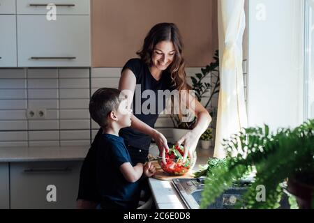 Little son helps mom cook vegetable salad in the kitchen