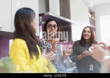 Women talking and drinking tea in kitchen - Stock Photo