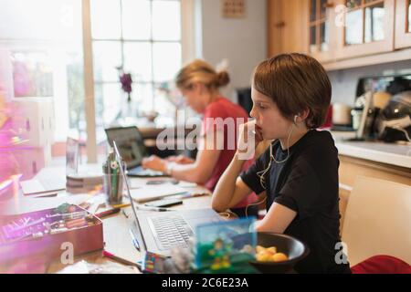 Focused boy homeschooling at laptop in kitchen - Stock Photo